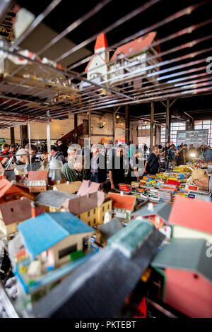15 September 2018, Berlin: Visitors to the 15th Berlin Railway Festival look at model railway stands in the Schöneweide depot. Steam trains are the focus of the two-day event. The association Dampflokfreunde Berlin presents more than 20 locomotives and wagons. Photo: Christoph Soeder/dpa - Stock Photo
