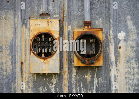 Two old electrical boxes sit empty of fuses and unused outside rusting in the elements - Stock Photo