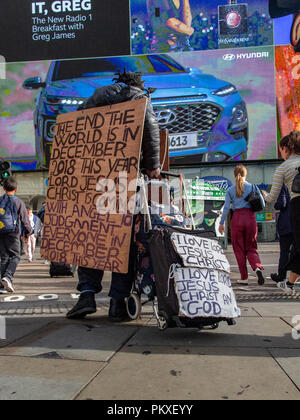 A man wearing a sandwich board predicting the end of the world walks through Piccadilly Circus in central London - Stock Photo
