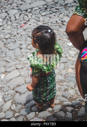 Small girl in traditional Mayan traje dress watched street parade in wonder on Dia de la Independencia 2018 (Independence Day) in Antigua Guatemala - Stock Photo
