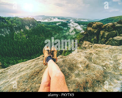 Hiker man take a rest on mountain peak. Male legs on sharp summit and hiker enjoy spectacular view. - Stock Photo