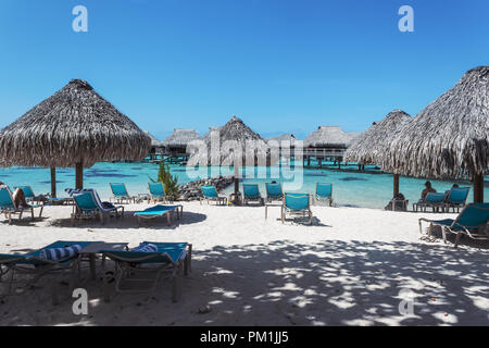 Tropical beach and over water bungalow in Moorea, French Polynesia - Stock Photo