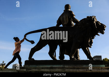 Victoria Memorial, London, UK, 17th Sep 2018. People form silhouettes as they pose next to the bronze 'man and lion' statue at Victoria Memorial, Buckingham Palace, against the bright blue sky in warm late afternoon sunshine. Credit: Imageplotter News and Sports/Alamy Live News - Stock Photo
