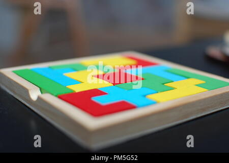 Colourful puzzle on black table makes great background. - Stock Photo