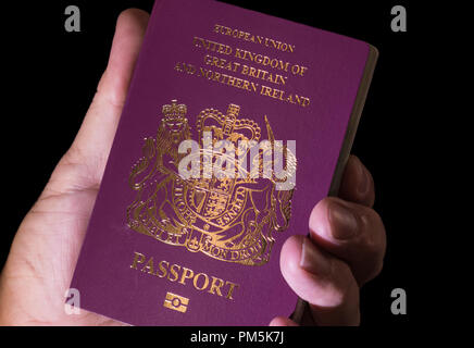 Hand holding a red European Union United Kingdom passport in 2018. - Stock Photo