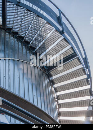 Abstract photo of a steel stairs turning up with a reflection of the stairs on a steel wall - Stock Photo