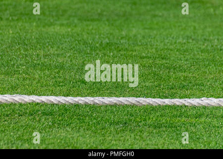 Rope marking the boundary of a rural village cricket pitch - Stock Photo