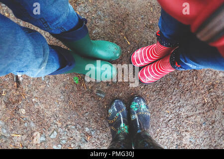 Three pairs of rubber boots at rainy autumn weather. View above - Stock Photo