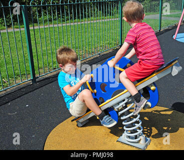 Two small boys playing on a see-saw in a play park. - Stock Photo