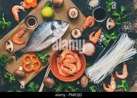 Ingredients for Asian dishes - raw Dorado fish, shrimp, rice noodles,mushrooms, vegetables, dark background, top view. Flat lay, toned photo - Stock Photo