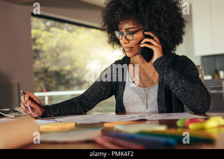 Businesswoman talking on smartphone and working in office. African female architect sitting at his workplace at home. - Stock Photo
