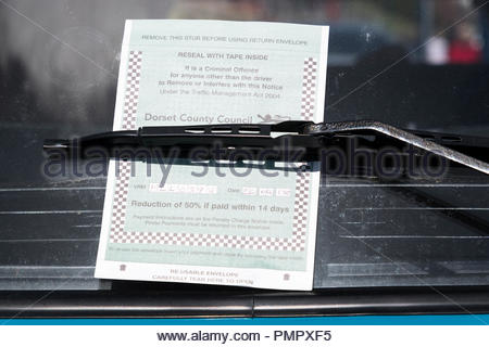 Close up image of a Dorset County Council parking charge notice under a car windscreen  wiper, Swanage, Dorset, England, UK - Stock Photo
