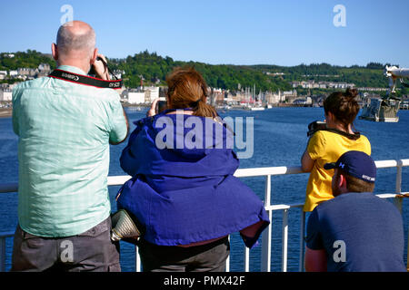 Capturing photographs of Oban as visitors arrive in the port on the Calmac ferry from the Isle of Mull - Stock Photo