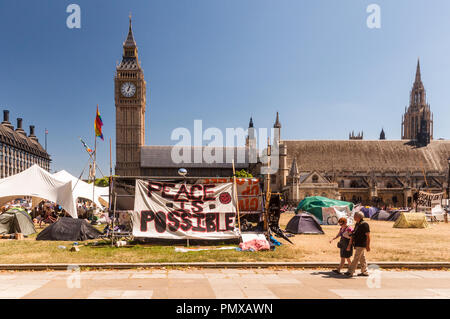 London, England, UK - July 4, 2010: Pedestrians walk past the Democracy Village protest camp occupying Parliament Square, outside the Houses of Parlia - Stock Photo
