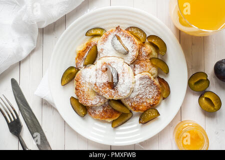 Cheese pancakes in powdered sugar with fresh plums on a plate. - Stock Photo