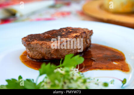 Grilled steak beef with sauce served on a white plate. Close up selective focus. - Stock Photo