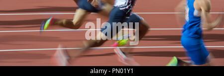 blurred motion group runners sprinters running on track stadium - Stock Photo