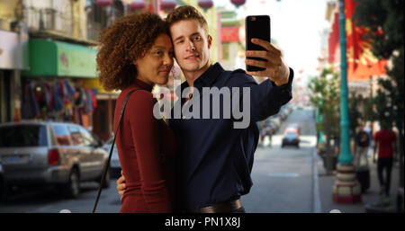 Happy mixed race couple using smartphone to take selfie in Chinatown - Stock Photo