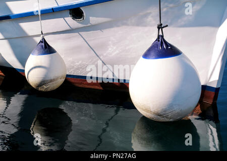Buoys and anchor ropes, close up. White buoys on fishing boat anchored in port. Mooring buoys, dock and fenders for boat protection. - Stock Photo