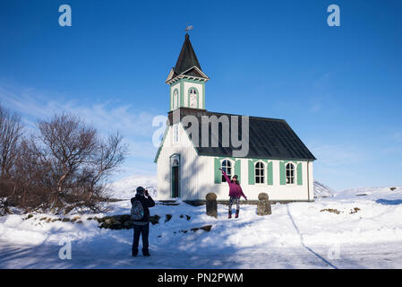 Tourist couple taking photograph at famous church chapel Pingvallakirkja in Thingvellir National Park - Pingvellir -  in Iceland - Stock Photo
