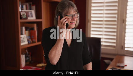 Older woman chatting on a cellphone with someone in home office setting - Stock Photo