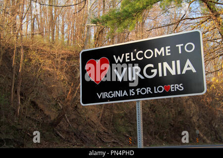 A roadside sign welcomes travelers along a rural road to the state of Virginia - Stock Photo