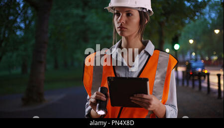 Woman worker in safety gear with tablet and flashlight outside in city park - Stock Photo