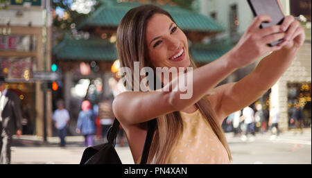 Woman in her 20s taking photo of herself with phone in San Francisco Chinatown - Stock Photo