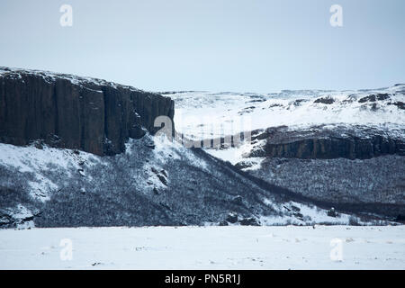 Typical dramatic Icelandic landscape of snow covered mountains of volcanic rock in winter in South Iceland - Stock Photo