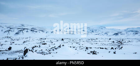 Empty landscape of mountains and snow-covered lava fields of volcanic rock by Sultartangastoo in the highlands of South Iceland - Stock Photo