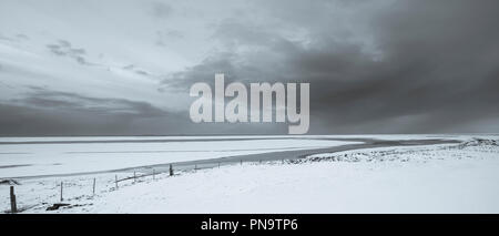 Wintry sun and puffy clouds above typical Icelandic snow-covered plains landscape towards the Atlantic Ocean near Hofn, South Iceland - Stock Photo