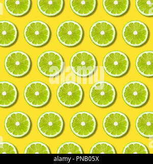 Green lime slices pattern on vibrant yellow color background. Minimal flat lay food texture - Stock Photo