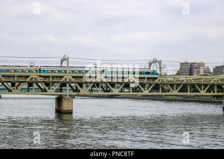 A Train on a Bridge over the Sumida River, Tokyo, Japan - Stock Photo