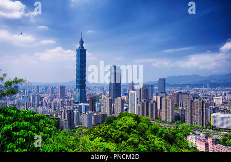 The Taipei 101 landmark building rising above generic architecture in the city of Taipei Taiwan on a sunny day as seen from Xiangshan or Elephant Moun - Stock Photo