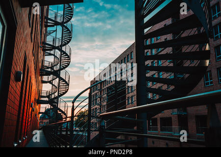 Spiral staircases in the old Warehouse District. Narrow canal and red brick buildings of Speicherstadt in Hamburg. After sunset - Stock Photo