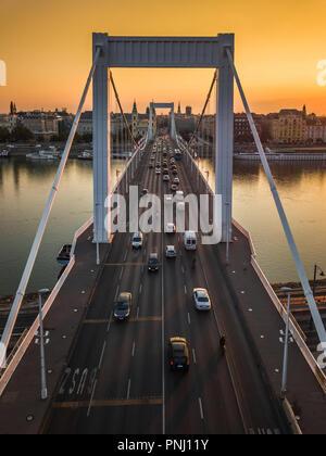 Budapest, Hungary - Beautiful Elisabeth Bridge (Erzsebet hid) at sunrise with golden sky and heavy morning traffic - Stock Photo