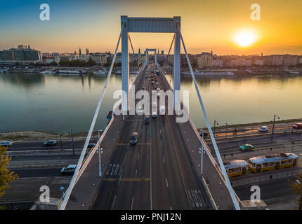 Budapest, Hungary - Beautiful Elisabeth Bridge (Erzsebet hid) at sunrise with golden and blue sky, traditional yellow tram and heavy morning traffic - Stock Photo