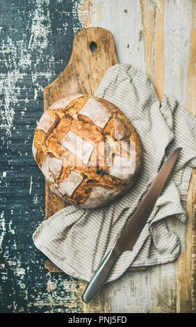 Flat-lay of sourdough wheat bread over linen napkin - Stock Photo