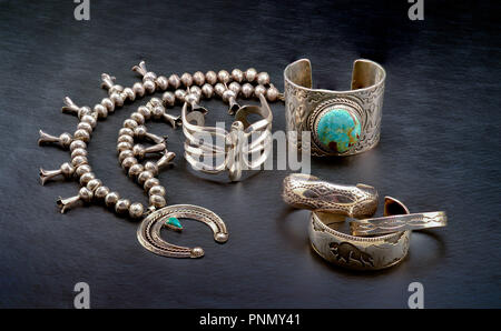 A Collection of Sterling Silver Native American Jewelry. Squash Blossom Necklace, Cuff Bracelet with large Turquoise Stone, and Three small bracelets. - Stock Photo