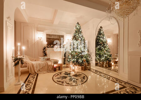 classical interior of a white room. Christmas evening by candlelight. classic apartments with a white fireplace, decorated christmas tree, sofa, large windows and chandelier. - Stock Photo