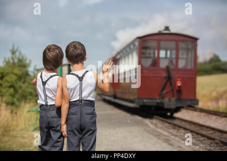 Beautiful children, dressed in vintage clothes, enjoying old steam train on a hot summer day in England - Stock Photo