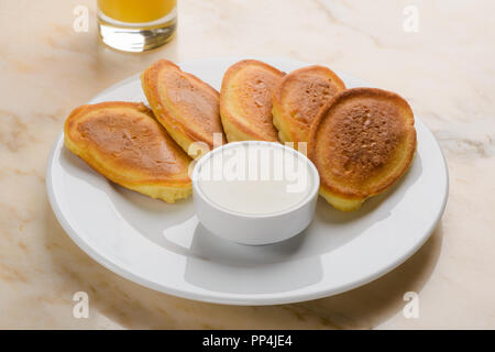 Pancakes served with sour cream - Stock Photo