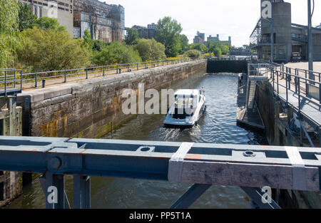 A small pleasure boat with a woman and young boy aboard navigating the Lachine Canal in the Montreal Old Port - Stock Photo