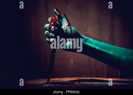 Halloween concept with Bloody stabbing. Hand with knife - Stock Photo