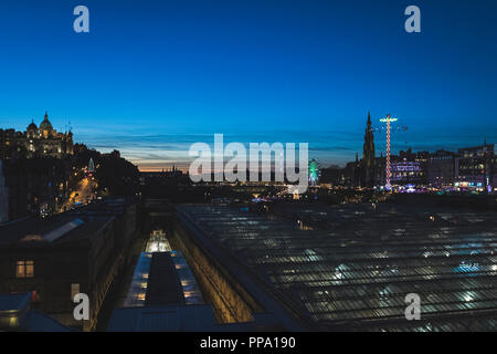 Edinburgh Castle and Christmas Market at twilight with view over train station - Stock Photo