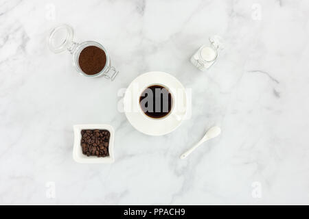 Black coffee in a cup, white sugar, ground coffee and coffee beans on white marble background. - Stock Photo