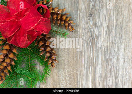 A red bow and three white pine cones on spruce boughs with copy space - Stock Photo