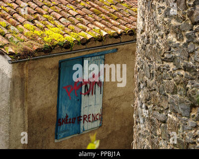 pattern of red graffiti on blue and white window shutters on rendered building with green tiled roof behind Seix castle in the Ariège Pyrénées, France - Stock Photo