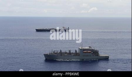 PACIFIC OCEAN (August 23, 2018) - MIlitary Sealift Command ships, the Watson-class vehicle cargo ship USNS Dahl (T-AKR-312) and the Lewis and Clark-class dry cargo ship USNS Lewis and Clark (T-AKE-2), sail in formation, August 23. HSC 25 is the Navy's only forward deployed MH-60S expeditionary squadron. As a part of Helicopter Sea Combat Wing Pacific, it provides an armed helicopter capability for U.S. 7th and 5th Fleets as well as detachments to various commands covering a diverse mission set. - Stock Photo