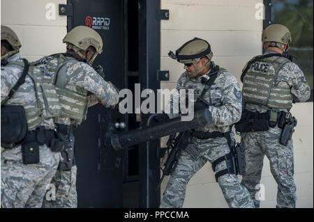 Members of the 6th Security Forces emergency services team (EST) breach an assault door during a training scenario at MacDill Air Force Base, Fla., Aug. 23, 2018. The new simulation house, opened on MacDill June 1, 2018, is used by EST and other community law enforcement partners such as Pinellas and Hillsborough County Sheriff's Offices. - Stock Photo
